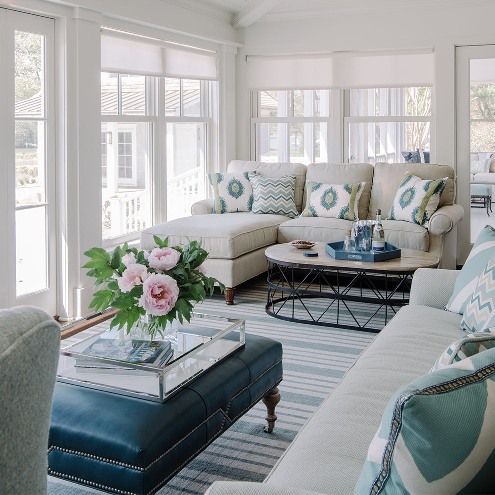 Jamie Merida Interiors project photo - sunroom with cream sofas, blue and white striped rug, blue leather ottoman