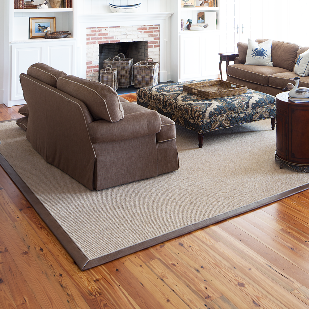 Custom cut area rug with a brown leather binding by Bountiful Flooring