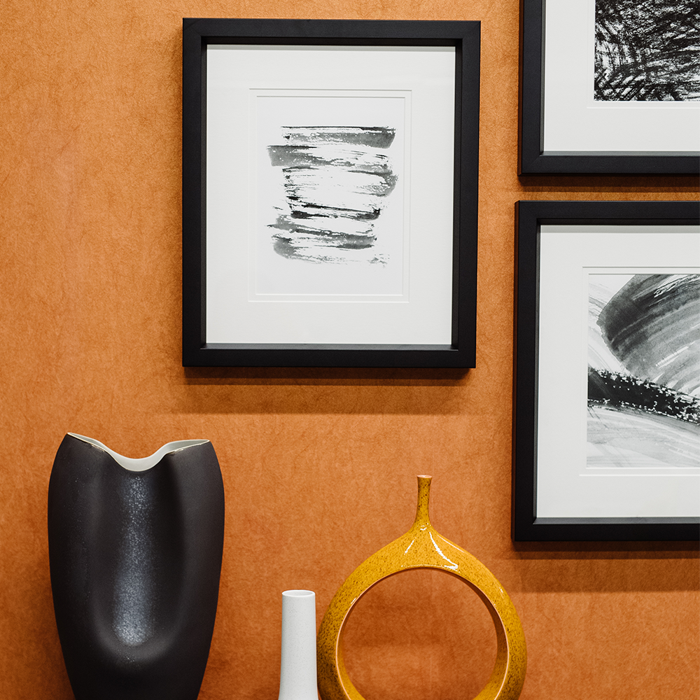 Cluster of black and white abstract art framed with white mats and black frames on an orange wall. Bountiful Framing