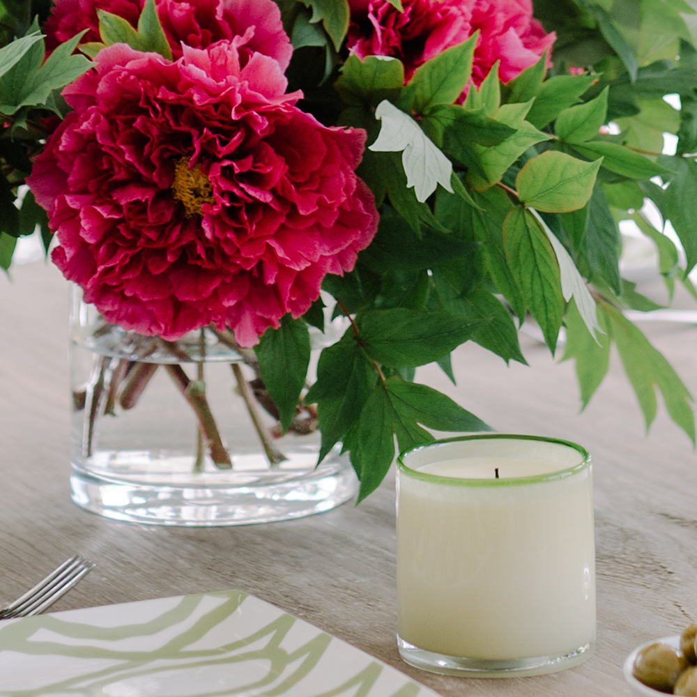Gifts at Bountiful Home - ivory candle with green rim in front of a vase of tree peonies
