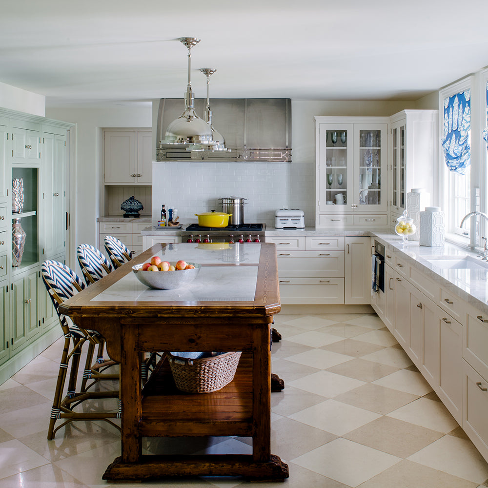 Kitchen design from Jamie Merida Interiors. Pictures green and white cabinets with a wood island and chrome finishes