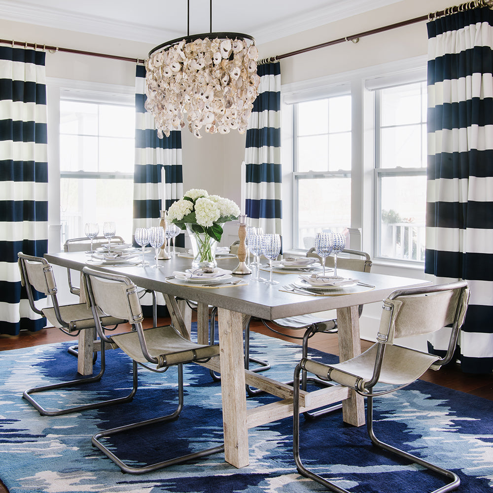 Blue and white dining room design by Jamie Merida Interiors - shows dining table, chairs, and oyster chandelier