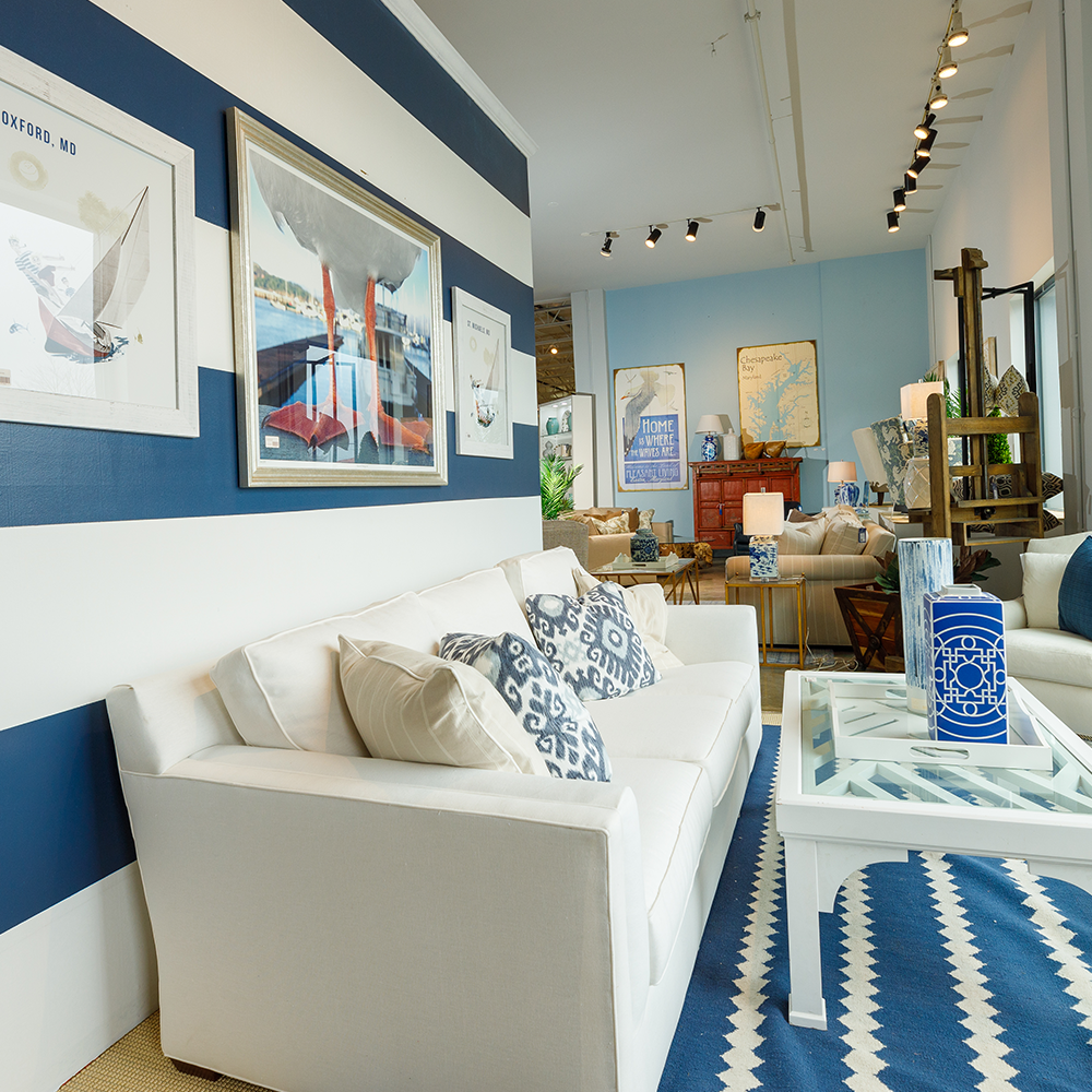 Bountiful Home store window - interior look at the window display - white couch with blue and white rug and striped wall