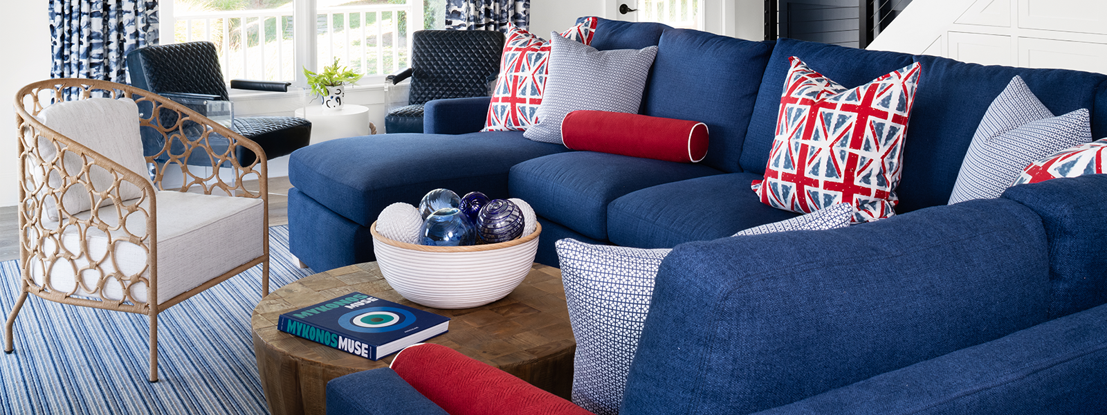 Close up of living room with blue sectional with union jack pillows and wicker side chair - Jamie Merida Interiors
