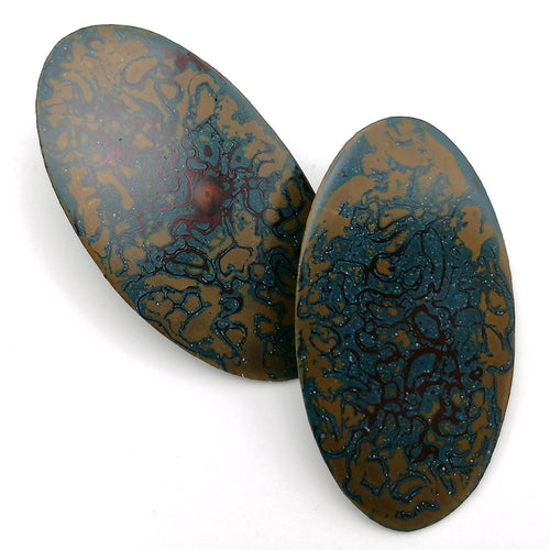 A pair of long oval statement earrings on a white background. Abstract pattern of blue and ochre yellow