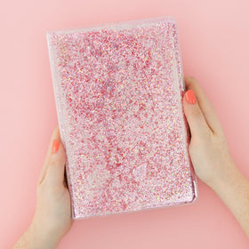 front of plastic covered journal with pink glitter and liquid inside front cover