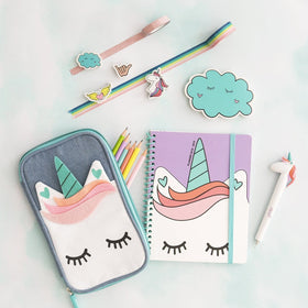 unicorn pen shown with unicorn pencil organizer, unicorn spiral notebook, unicorn pencil sharpener, ribbon tape and pastel pencils