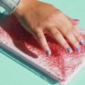 video of pink liquid glitter journal shown with hands interacting with the liquid glitter moving it around on front cover