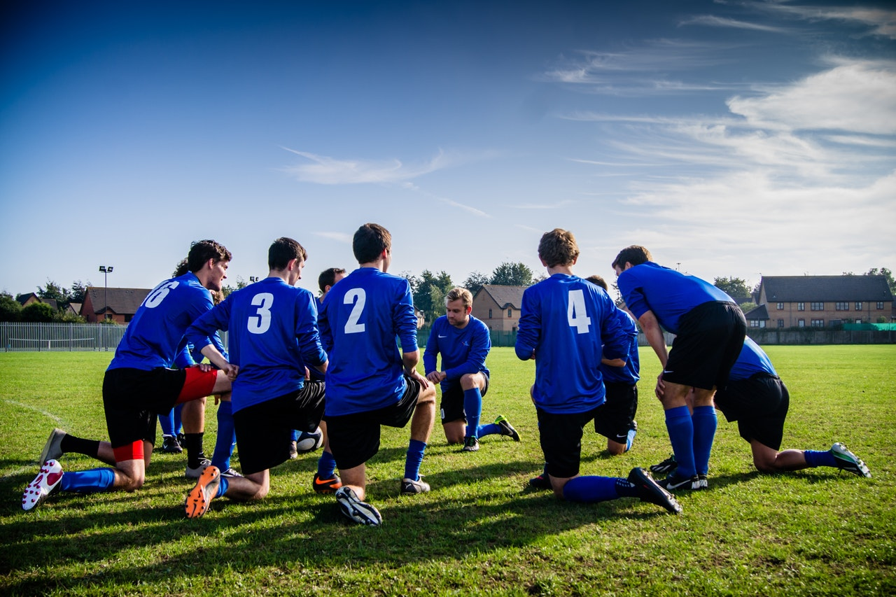 Youth soccer team kneeling down, with their numbers visible.