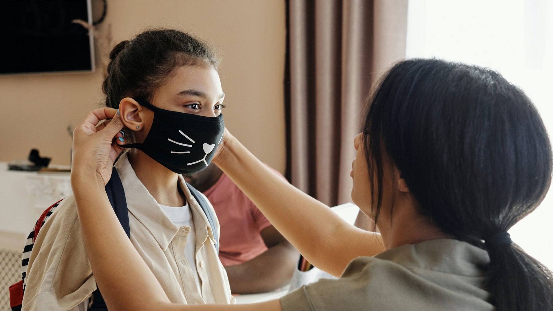 A mother puts a face mask on her daughter.