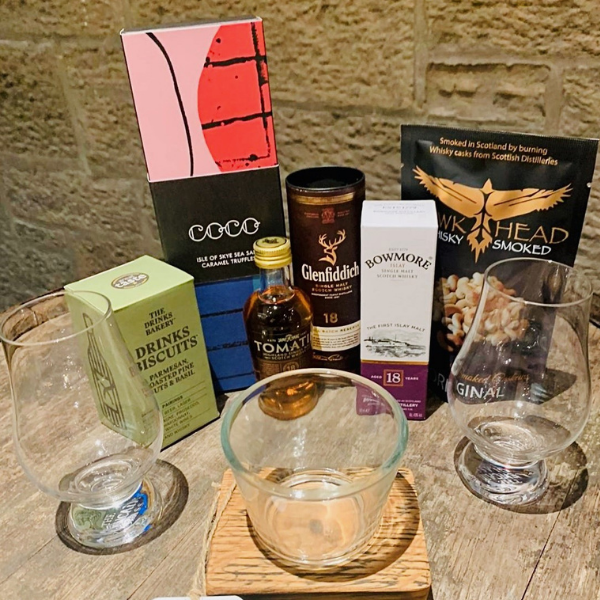 Valentine's lockdown whisky box - Tomatin 18 5cl, Glenfiddich 18 5cl, Bowmore 18 5cl, 2 Glencairn crystal glasses, box of Isle of Skye chocolate truffles, box of Drinks Bakery biscuits - parmesan, toasted pine nuts and basil flavour, packet of Hawkhead whisky smoked cashew nuts, whisky stave candle light holder.