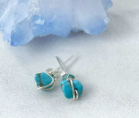 pair of sterling silver turquoise studs next to blue agate geode