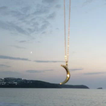 Video of the gold crescent moon necklace with a real moon and the sea - representing the power of the moon