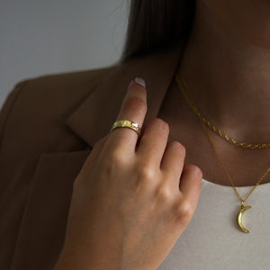 Hammered texture gold ring styled with layered chain necklaces