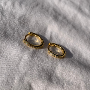 Sparkly diamond-like cubic zirconia stones on gold huggie hoop earrings in sunlight