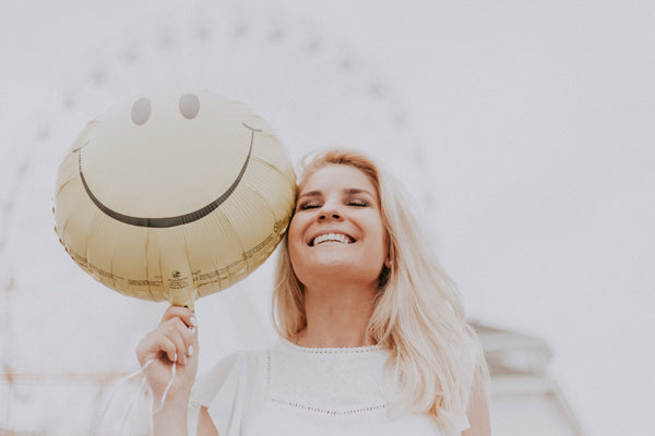 Smiling woman holding a happy face balloon