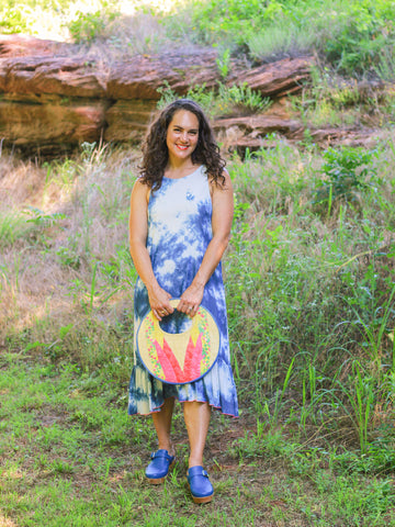 Woman wearing a tie dye dress, blue clogs, and holding a vintage woven handbag. Her backdrop is red rock outcroppings and green grass.