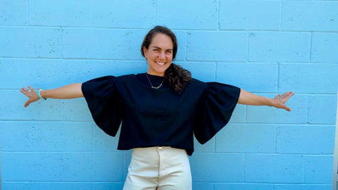 Girl smiling in a black linen top with flutter sleeves and white shorts. The background is blue.