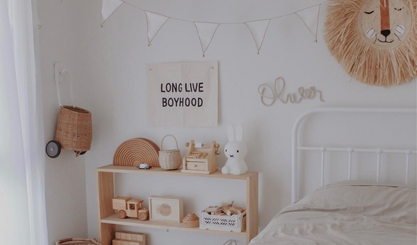 A neutral kids bedroom with wooden and rattan decor. Perfect for play based learning. Read more about it at Little Gatherer Children's Boutique NZ