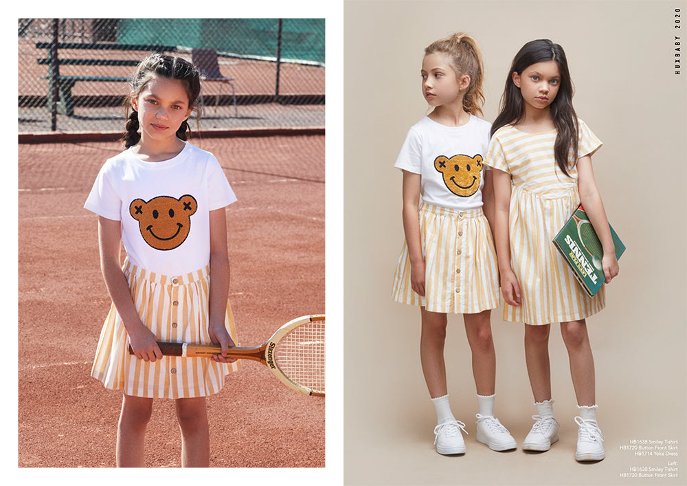 Girl wearing new season Huxbaby Be Happy Collection. Playing Tennis in striped skirt and smiling top.