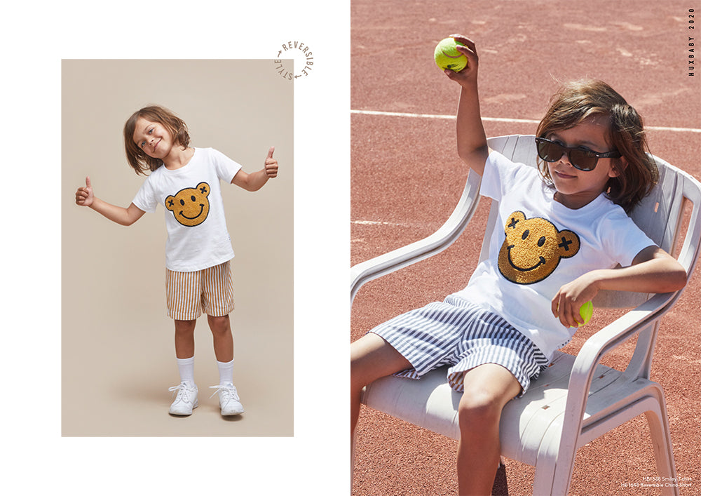 Boy wearing reversible shorts and smiley t-shirt from the new season Huxbaby Be Happy Collection.