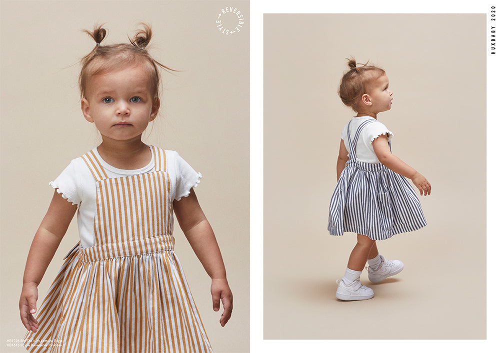 Toddler girl wearing reversible striped dress from the new season Huxbaby Be Happy Collection.