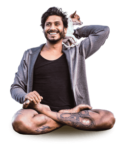 yoga teacher Jai Sugrim sitting in a cross-legged position with a small dog on his shoulder