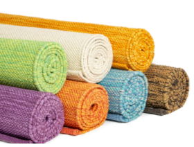 Rolled up cotton yoga mats stacked together