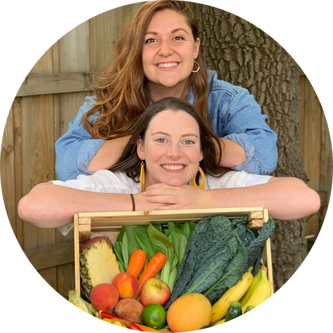 Image of Vic and Caity smiling behind a box of fresh fruit and vegetables.