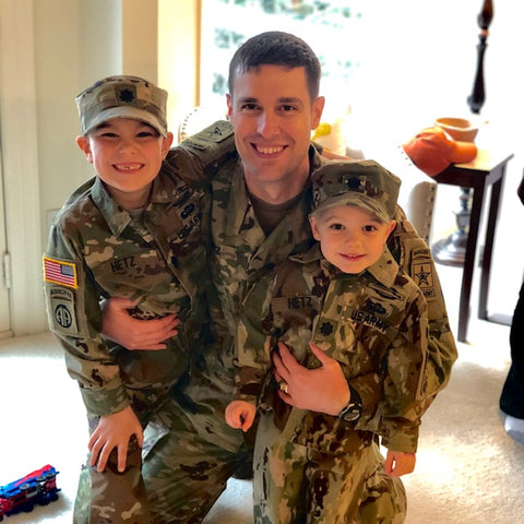 Kids Cake Boxes are also a way to bring military friends together. Keep connected to those loved ones back in the States or at your old duty station by sharing cake kits. Picture of military father with young sons in uniform.