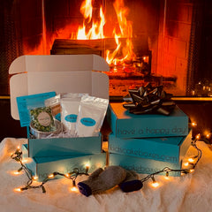 Image of Kids' Cake Boxes cake kits in front of a warm fire/winter scene as an idea for virtual holiday gathering