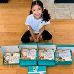 Child displaying many Kids Cake Boxes to use as an idea for a virtual birthday party or as an idea for a virtual play date