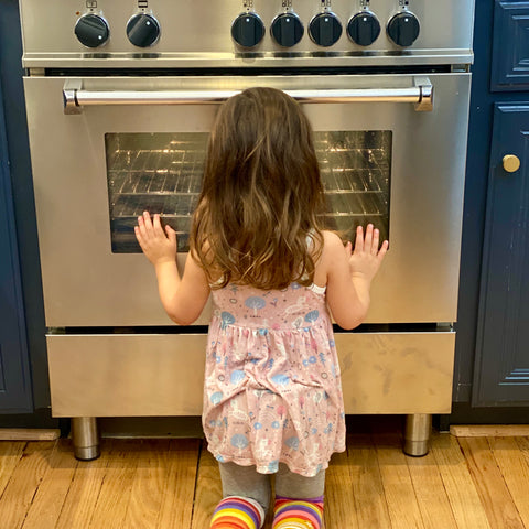 Image of young girl waiting at oven door for Kids' Cake Boxes to be done baking. Kids' Cake Boxes, cake kits for virtual parties