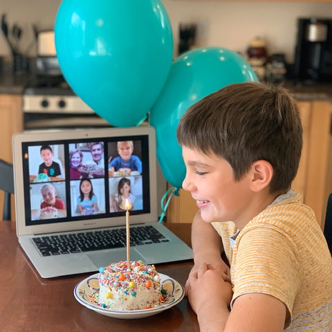Kids Cake Boxes. Ideas for virtual birthday party. Picture of boy on Zoom birthday with his cake kit from Kids Cake Boxes.