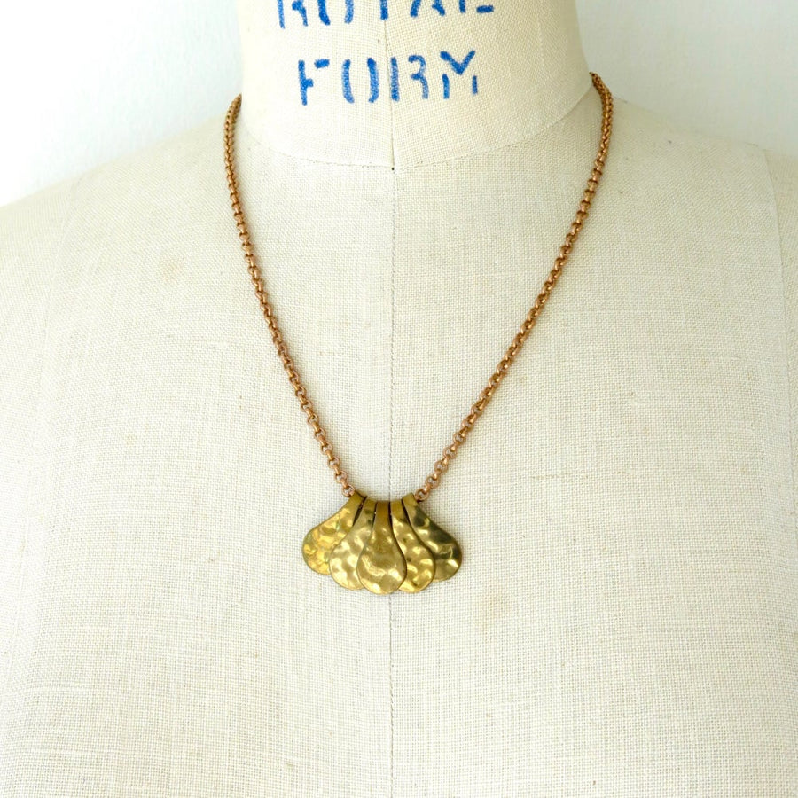 Fragment Necklace with five pieces that work together to form a pendant. The pieces slide freely along a brass chain.