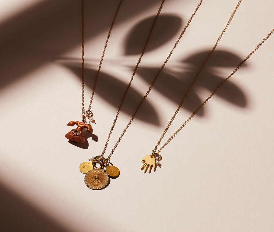 Share a greeting with the Hello, Token or Hi Five Necklaces made with brass charms and freshwater pearl.