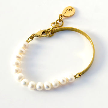 Illuminated Bracelet with one half consisting of a string of pearls and the other half a solid brass band.