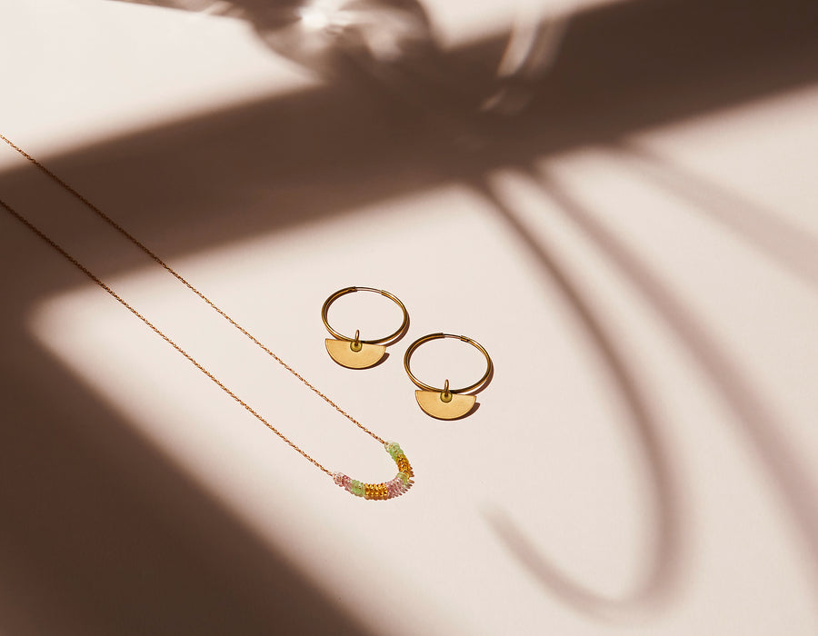Inner Circle Hoop Earrings and Necklace are made with brass and feature glass donut loop accents.