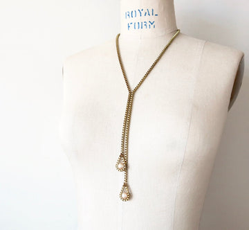 Lustrous Necklace by MoonRox is a Y-style necklace featuring vintage glass pearls bound by brass box chain.