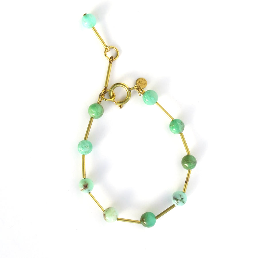 Resilience Bracelet made of round semi-precious stones staggered with brass tubes. Shown in chrysoprase.