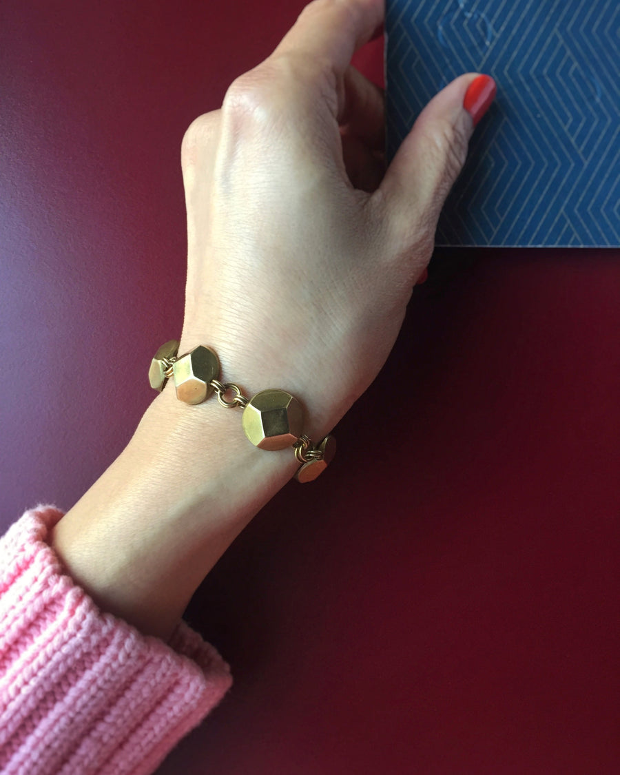 Reverie Bracelet by MoonRox Jewellery & Accessories shown on wrist. This elegant bracelet features faceted brass jewel shapes.