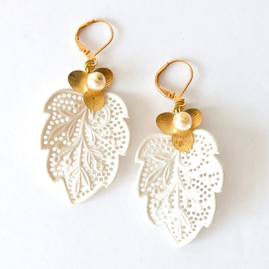 Secret Garden Earrings by MoonRox Jewellery & Accessories showcase white vintage celluloid lace leaves accented with brass flowers and glass pearls.
