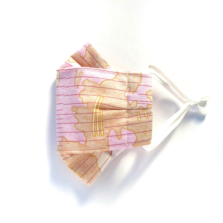 Shoreline Folded Non-Surgical Reusable Fabric Mask with adjustable ear loops. Made with three layers in central panel. Pink and peach pattern on 100% cotton. Handmade in Toronto, Canada.