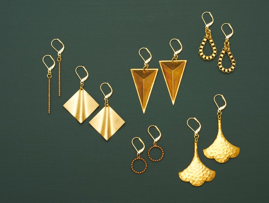 Twist Earrings are shown with the Undulate, Monument, Bound, Hammered Swish and Stippled Loop Earrings. Your choice of brass charm earrings.