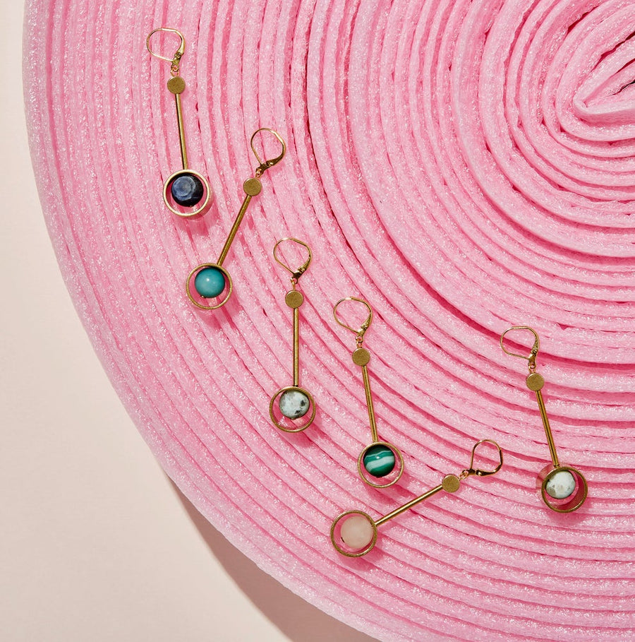 Wander Earrings are modern long brass earrings with semi-precious stones housed inside circular forms at the base. Choose from many different semi-precious stones.