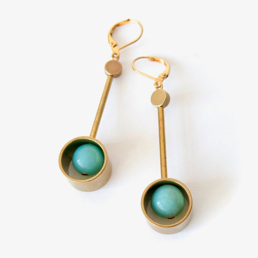 Wander Earrings are modern long brass earrings with semi-precious stones housed inside circular forms at the base.