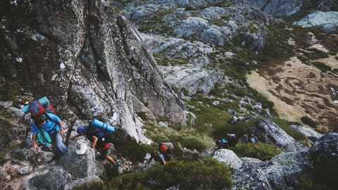 three backpackers scaling a mountain