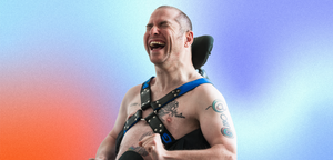 Andrew Gurza laughing on gradient background Chief Disability Officer, Handi