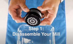 Step 1: Completely Disassemble Your Mill - hand holding Flower Mill Premium Grinder Over glass container and blue cloth