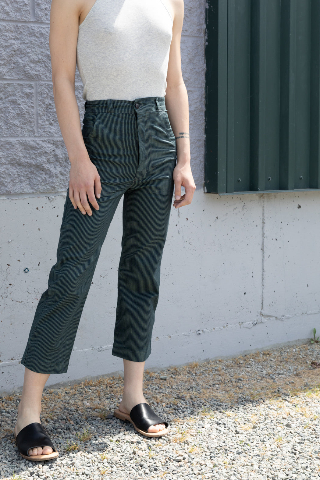 Photo of a a lightweight, super stretchy, striped dark green denim culotte with a high waist and button closure.